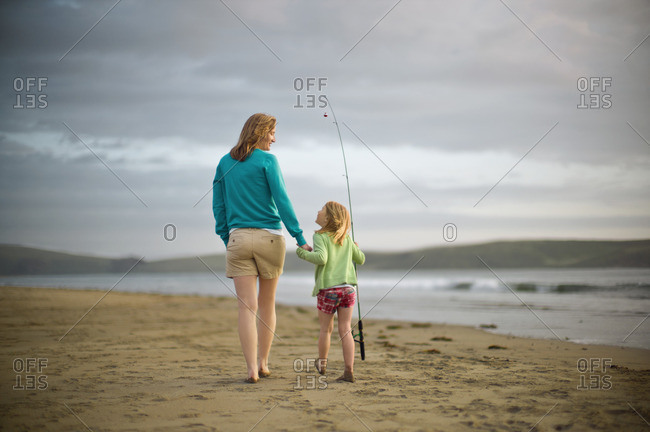 Mother and daughter walking on the beach with a fishing rod.