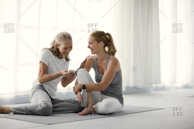 Two friends laughing together in a yoga class.