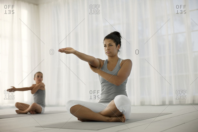 Mother and daughter practicing yoga together.