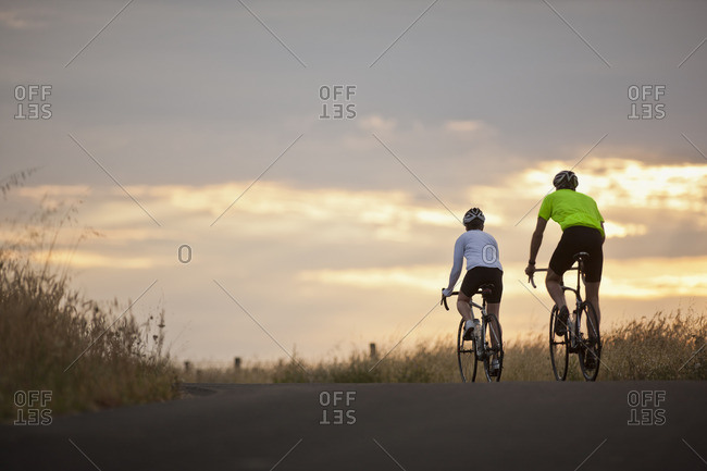 Two people cycling together on a rural road.