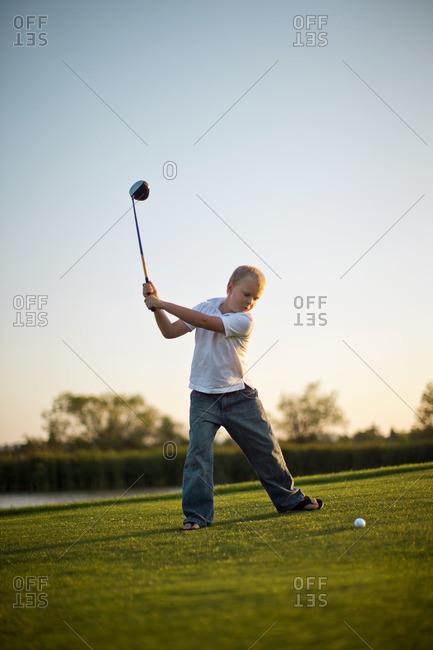 Young boy swinging a golf club.