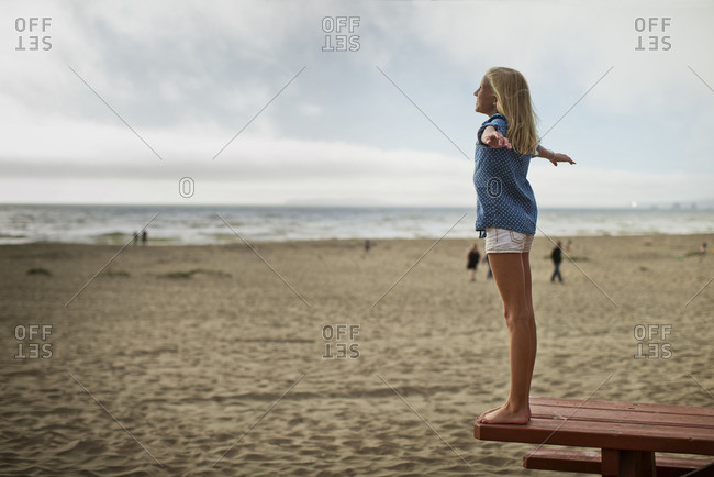 Young girl standing on a picnic table at the beach.