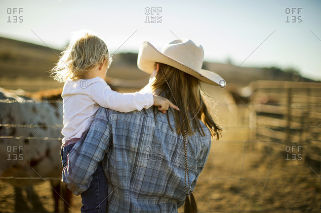 Mother and daughter looking at horses on a ranch.