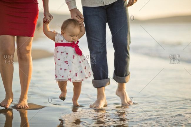 Parents walking with their baby girl on the beach.