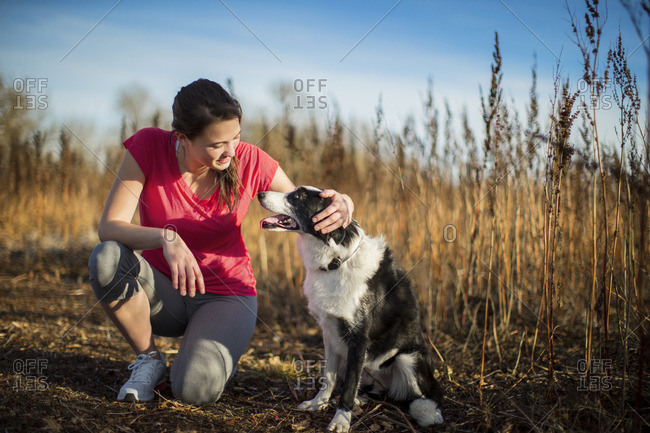 Woman petting her dog while out on a walk.
