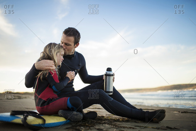 Father and daughter relaxing after a body boarding session at the beach.