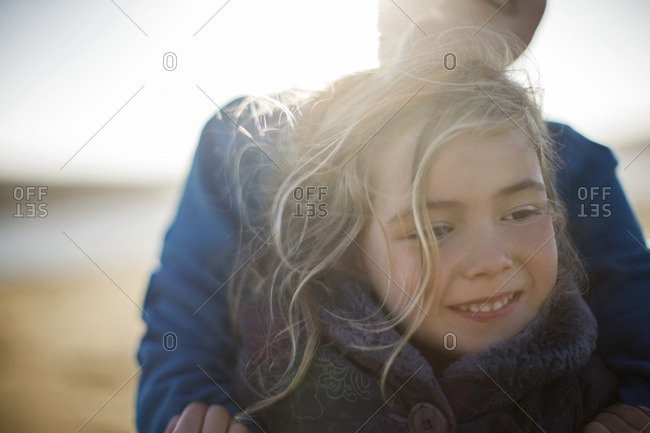 Young girl being hugged by her father at the beach.
