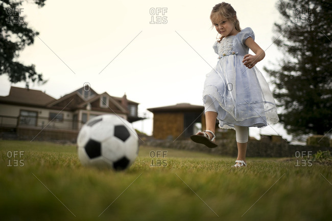 Young girl playing with a soccer ball.