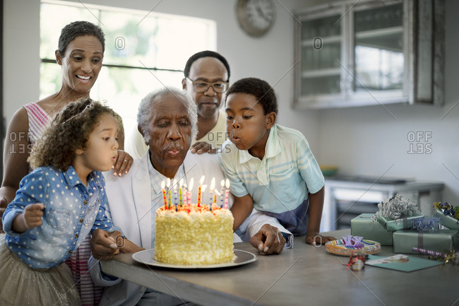Senior man blowing out the candles of his birthday cake, with the help of his family.