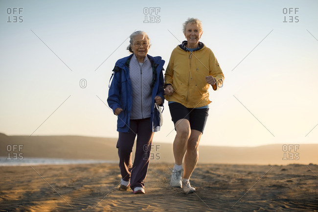 Two senior friends jogging together on the beach.