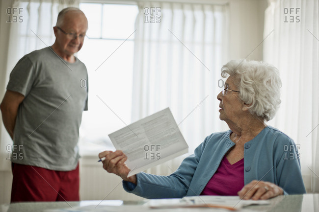 Senior woman confronting her husband about a household bill.