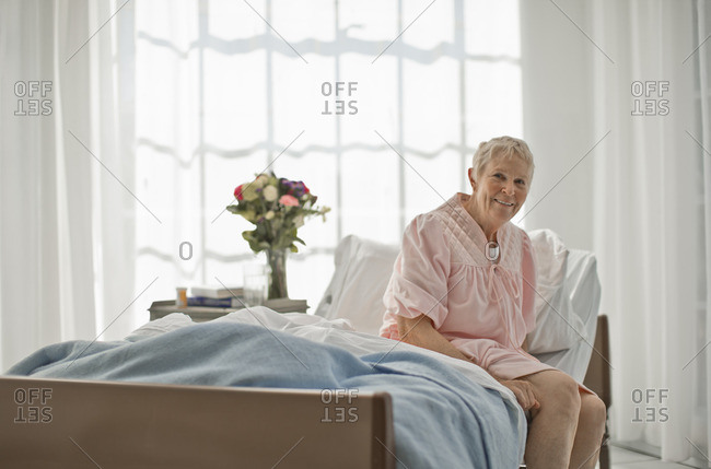 Smiling senior woman sitting on her bed.