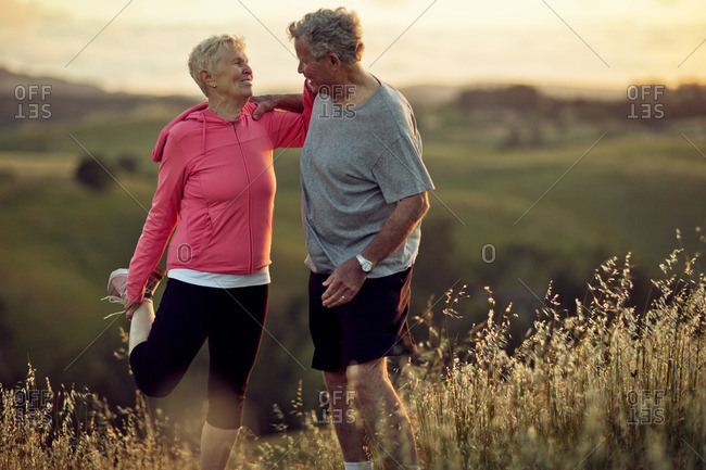 Senior couple stretching while out exercising.