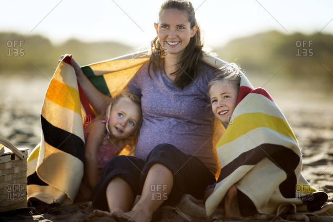 Pregnant woman sitting on the beach with her two daughters.