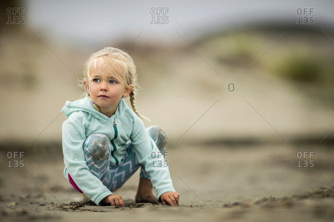 Young girl playing on the sand at the beach.