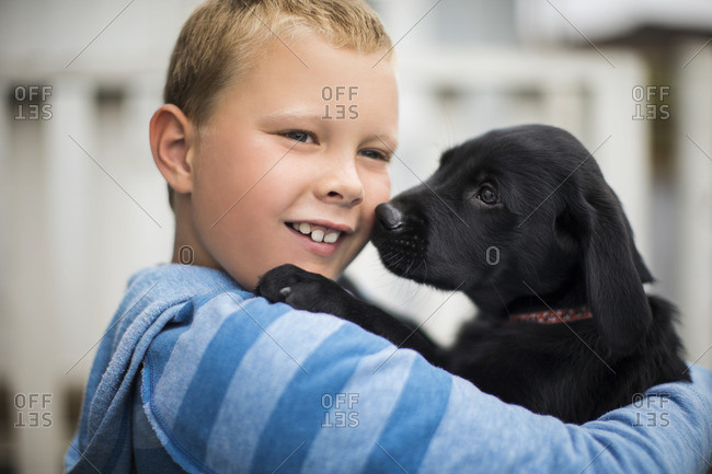 Young boy hugging his puppy.