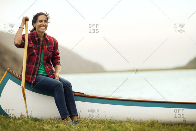 Woman sitting on a canoe by a lake.