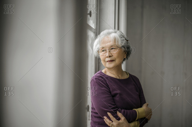 Senior woman looking out of the window.