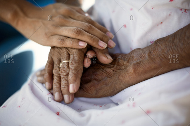 Nurse holding hands with an elderly patient.