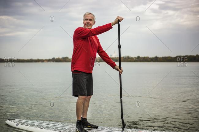 Senior man paddleboarding.