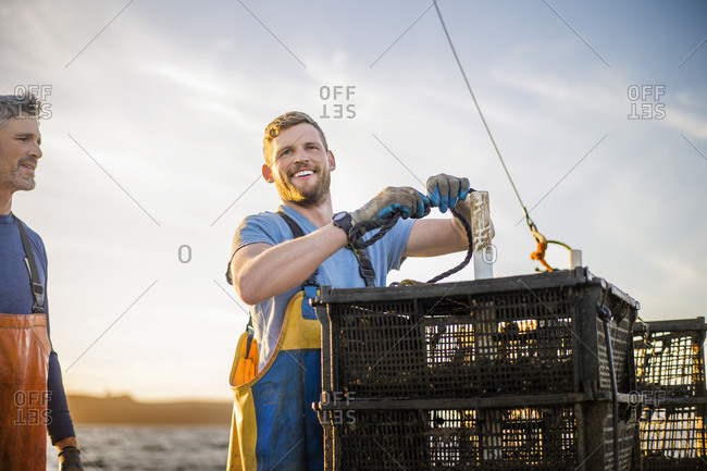Fisherman catching lobsters on a boat.