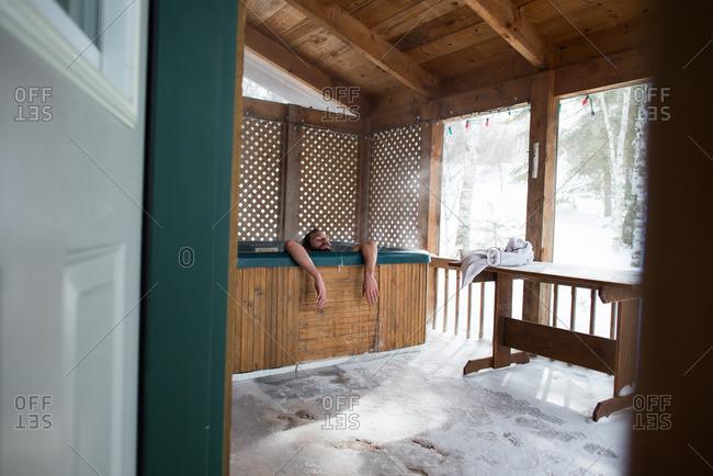 Soaking in a hot tub in a winter cabin