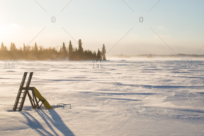 Ladder stands in frozen winter lake as snow blows across