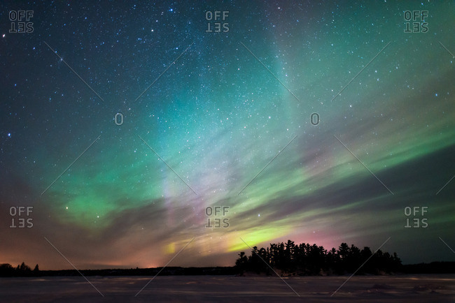 Northern lights dancing across winter sky