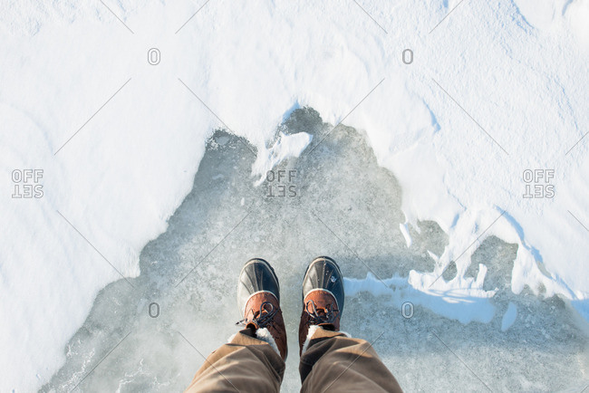 Man's boots standing over frozen lake and snow