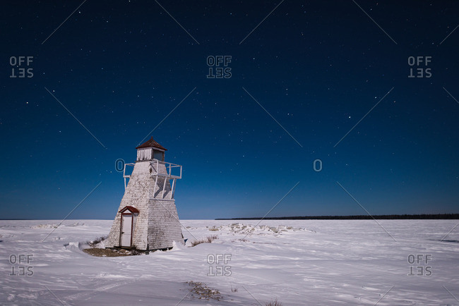 Nighttime over abandoned lighthouse in winter