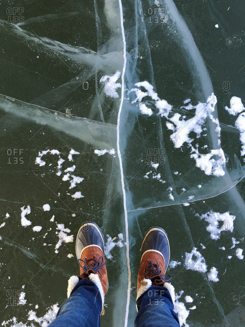 Man's boots standing over frozen lake
