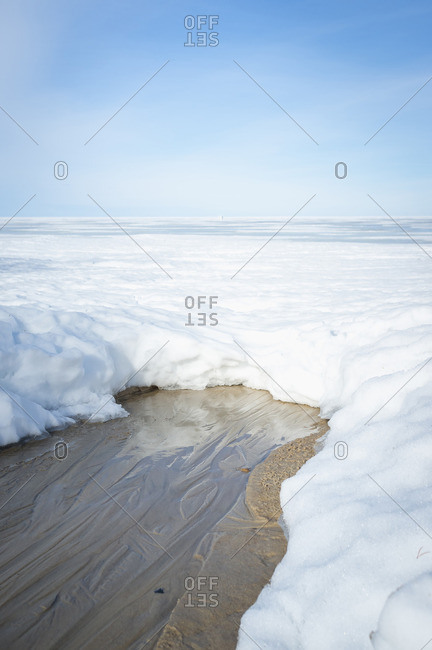 Sandy beach and water peek out from underneath thick blanket of snow
