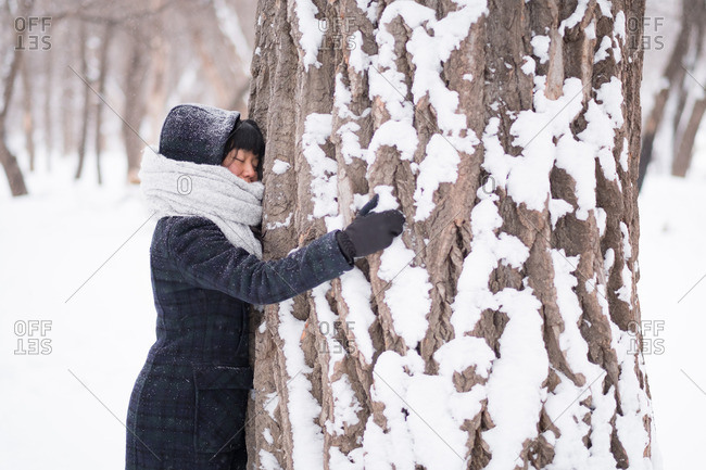Woman quietly embracing large tree in snowy winter