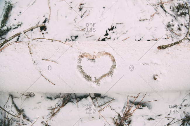 Heart drawn in the snow on a fallen tree