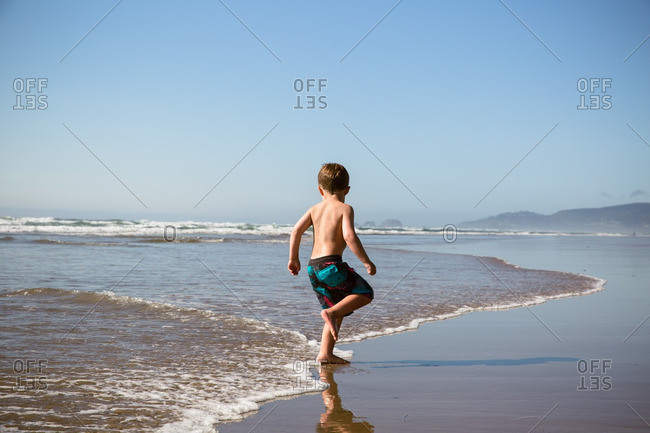 Boy playing in the waves of Cape Lookout in Oregon