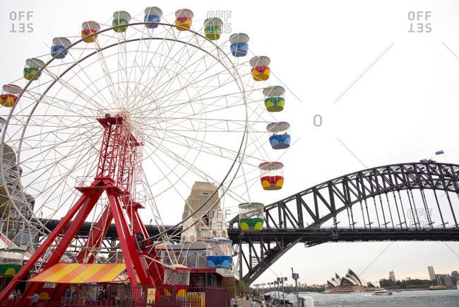 Sydney, Australia - December 11, 2015: Ferris Wheel at an amusement park by a bridge in Sydney, Australia