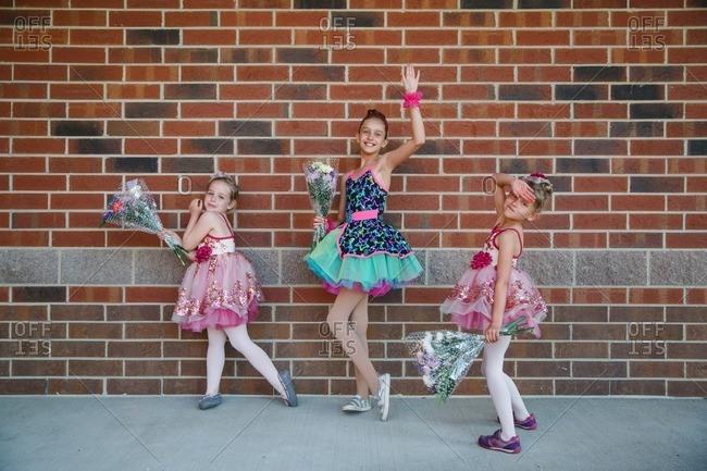 Three girls posing in dance recital costumes