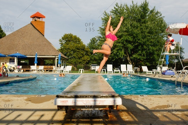 Young girl jumping off pool diving board