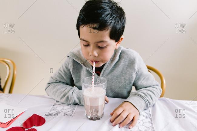Little boy blowing bubbles in his milk.