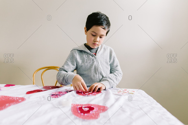 Little boy making a Valentine\'s Day cards.