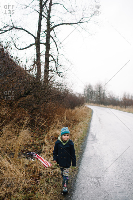 Young girl walking at edge of road with American Flag