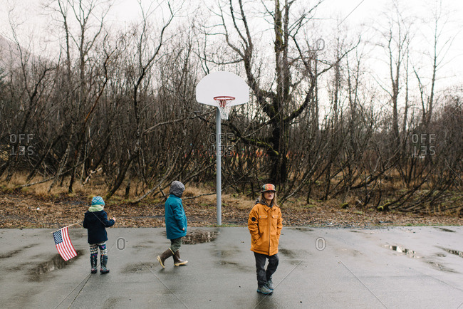 Children playing on basketball court in rainy weather
