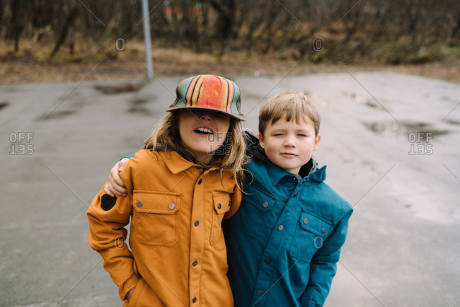 Portrait of two young brothers on rainy basketball court