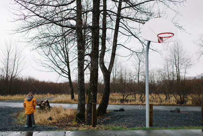 Boy standing at edge of basketball court in rainy weather