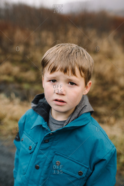 Portrait of young boy in blue coat in fall