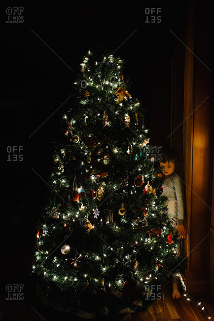Child in dark room standing by decorated Christmas tree