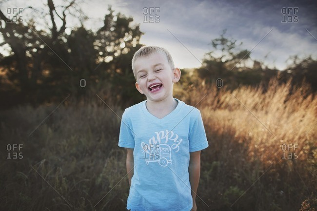 Boy laughing in sunny rural field