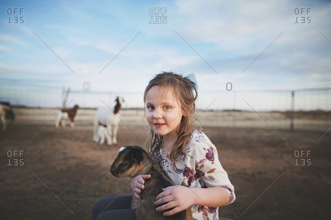 Girl in a pasture holding goat
