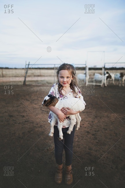 Girl holding a goat in pasture
