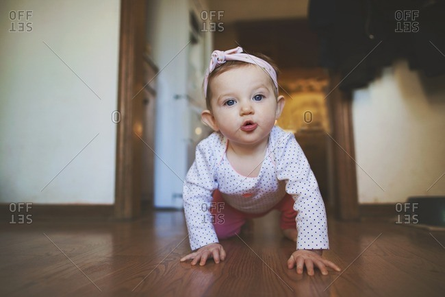 Toddler girl crawling inside home